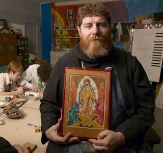 Photo of Fr. Daniel holding an Icon he painted.
